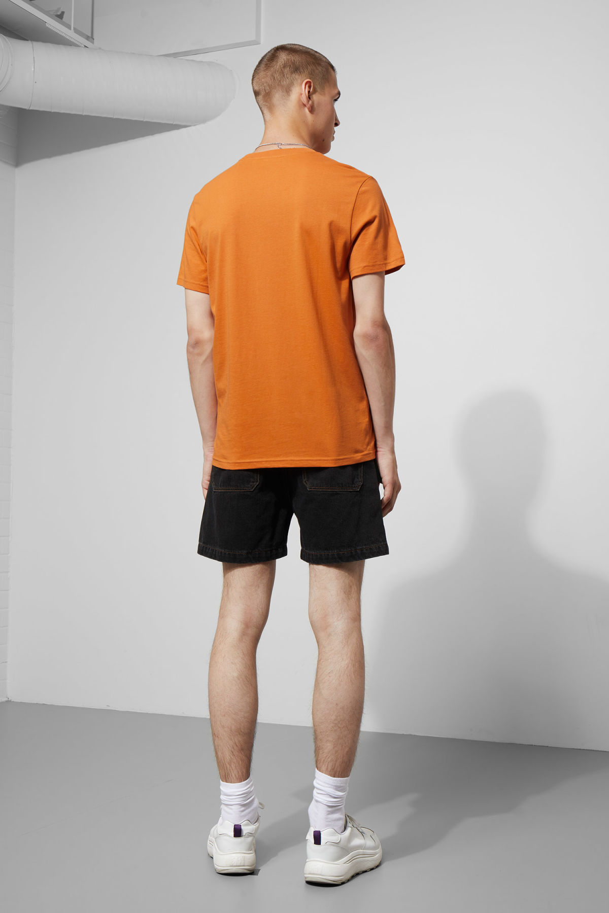 Model side image of Weekday alan t-shirt in orange