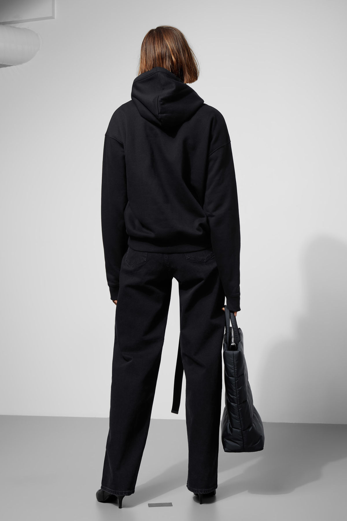 Model side image of Weekday ailin hooded sweatshirt in black