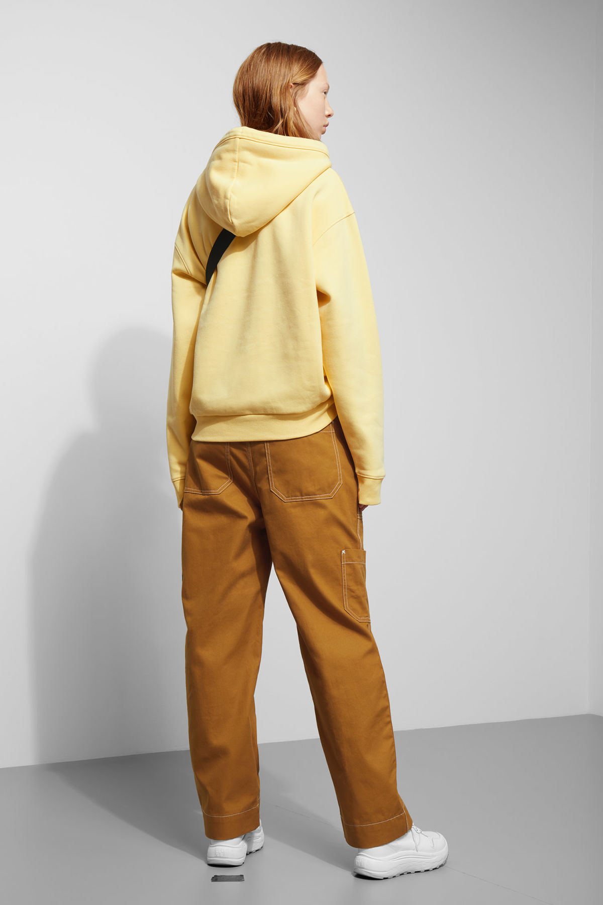 Model side image of Weekday ailin hooded sweatshirt in yellow