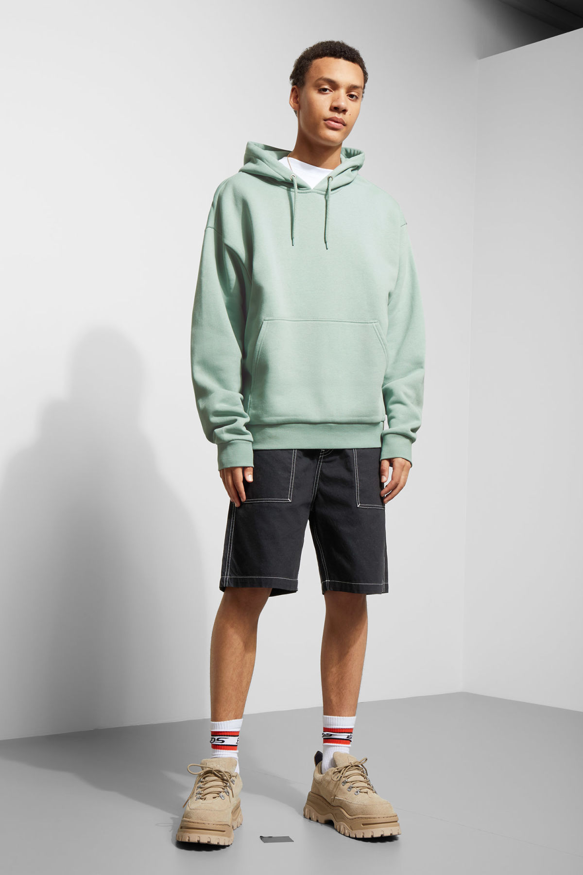 Model side image of Weekday big hawk hoodie in turquoise