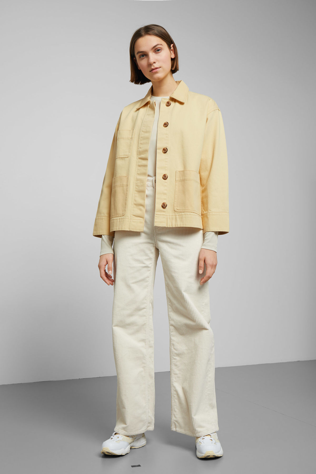 Model side image of Weekday ina jacket in yellow