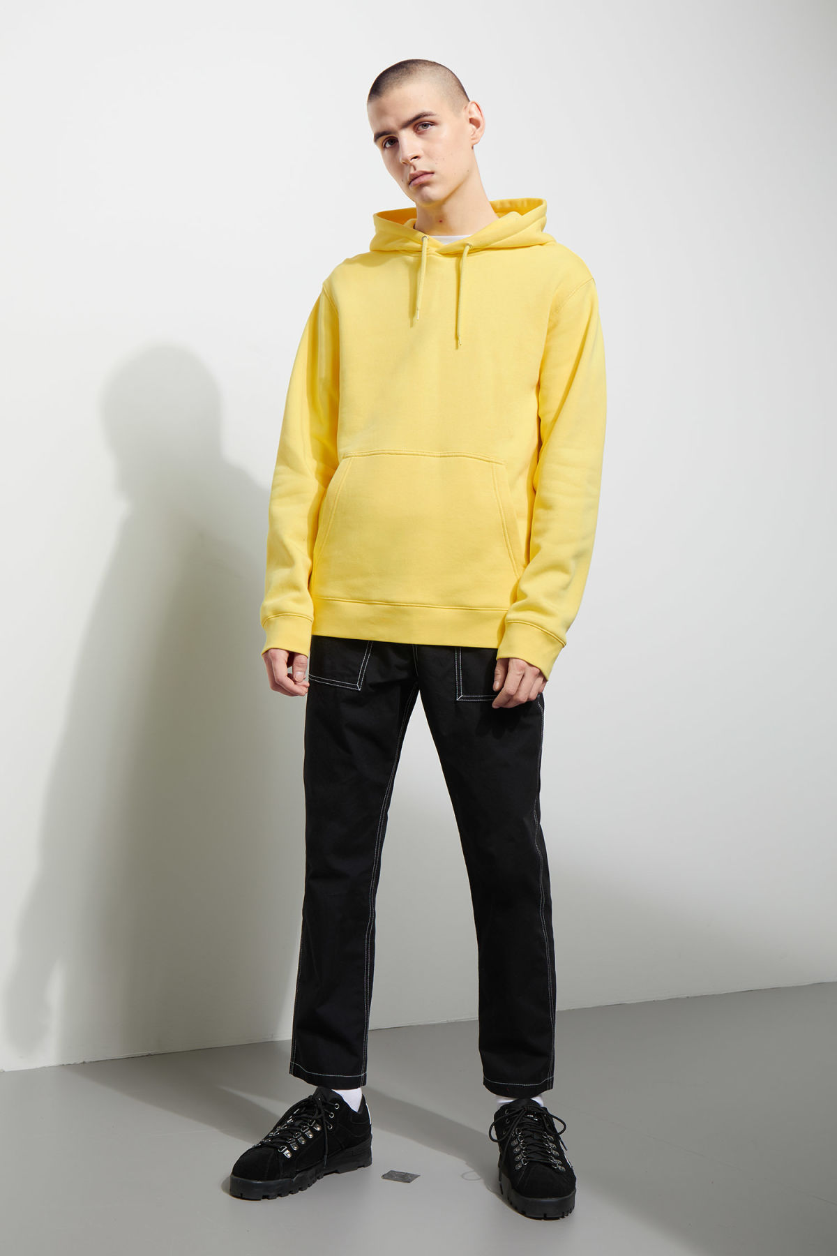 Model side image of Weekday hawk hoodie in yellow