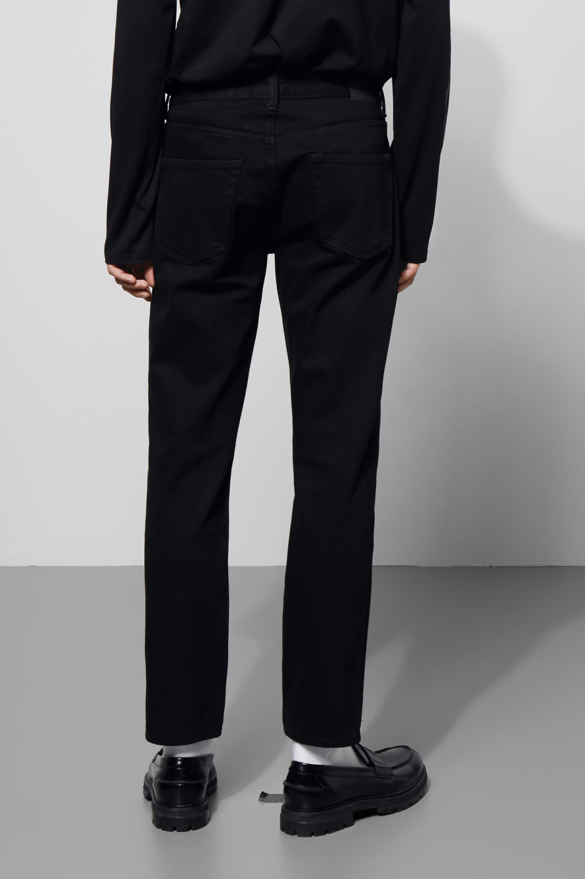 Model side image of Weekday vacant rinsed black jeans in black