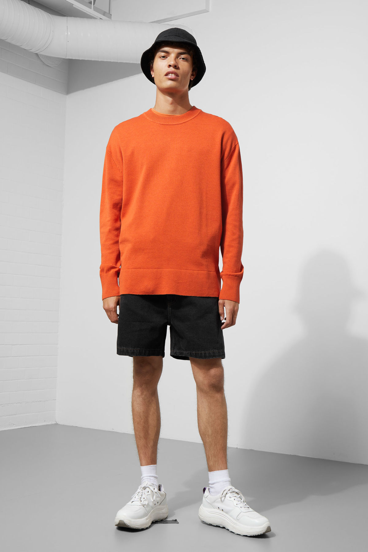 Model side image of Weekday earl cotton sweater in orange