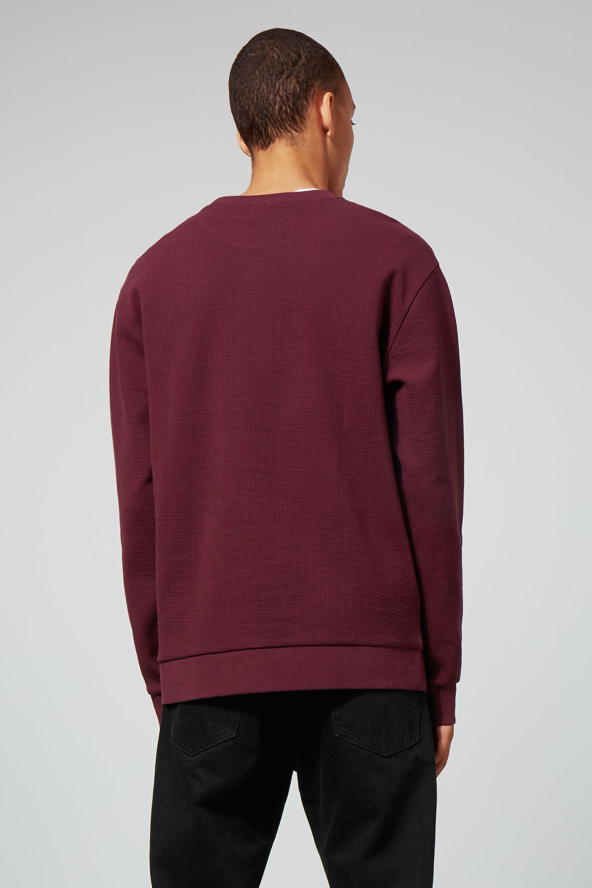 Model side image of Weekday steve structured sweatshirt in red