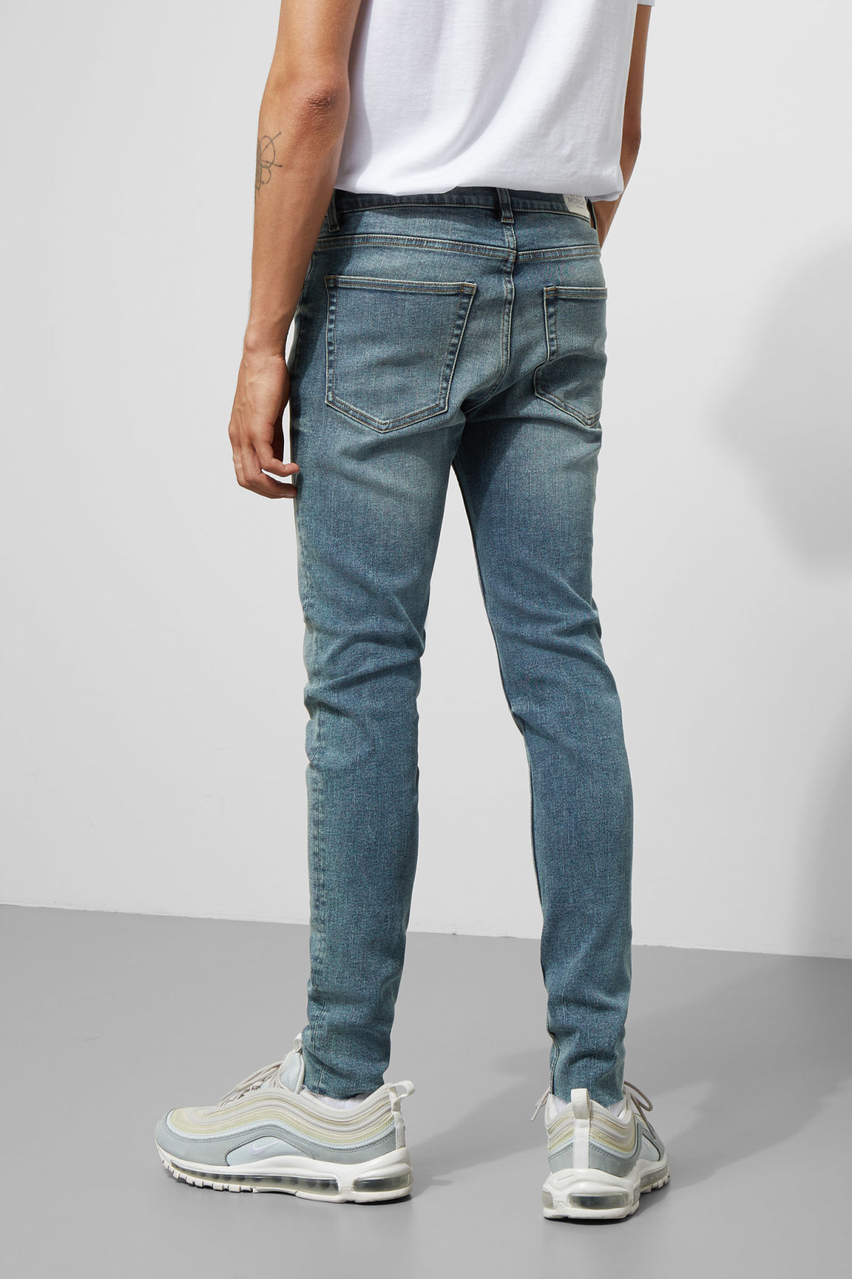 Model side image of Weekday him spray blue stain jeans in blue