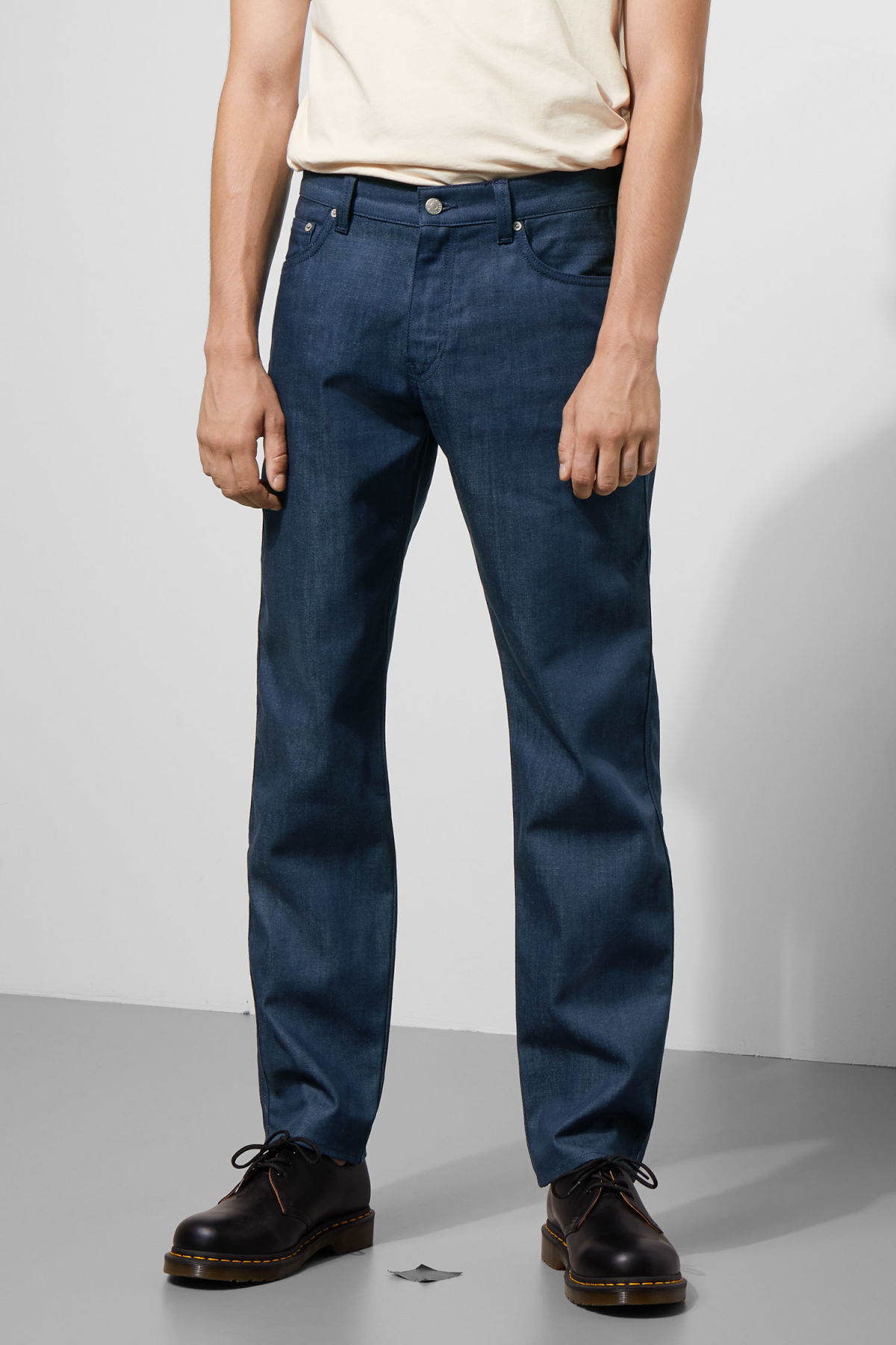 Model side image of Weekday tennesse raw denim trousers in blue