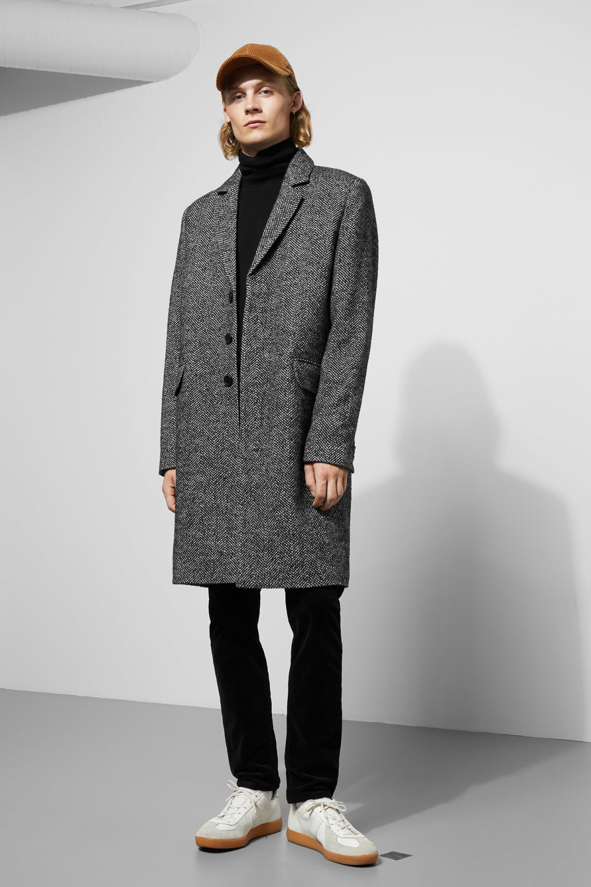 Model side image of Weekday spencer herringbone coat in black
