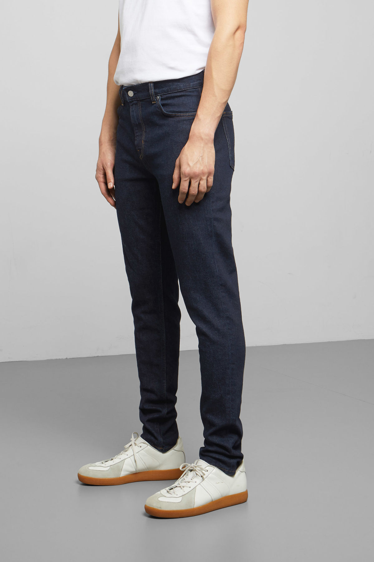 Model side image of Weekday cone dark rinse jeans in blue